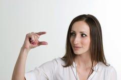 Seriouse妇女显示与在白色隔绝的手指的大小 库存图片
