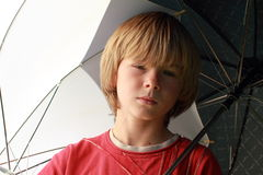 Seriouse boy with umbrellas Stock Images