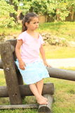 Seriouse girl sitting on wooden construction. Seriouse barefoot girl in blue skirt and pink t-shirt sitting on wooden construction of swing on playground Stock Photo