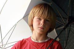 Seriouse Junge mit Regenschirmen Stockbilder