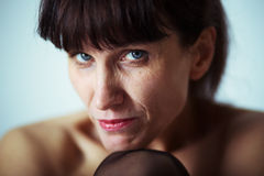 Seriouse mature woman. Serious mature woman with bared shoulders looking at camera Stock Photography