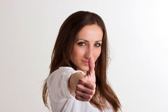 Serious Woman is Showing Nr.1  on White Background. Serious Woman is Showing a Nr.1 with Her Thumb  on White Background Stock Photo