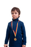 Seriously little boy with gold medal at his neck isolated on white Royalty Free Stock Photo