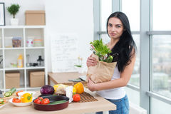 Seriously looking girl holding paper bag from market full of green fresh vegetables. Woman practicing diet and healthy Stock Photos