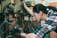 Seriously milling machine factory female worker. Looking at steel process parts and adjusting industrial machine to drilling position Stock Photos