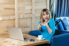 Portrait of unbelievable young girl freelancer with blonde bob haircut hair in blue blouse are sitting in cafe, working on laptop stock photo