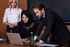 Seriously spirited people while working. Look into the laptop. Young pretty business women in black robe sitting between secretary and manager using the laptop Royalty Free Stock Photos