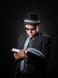 Seriously teenage boy dressed in suit reading book Stock Photo