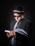 Seriously teenage boy dressed in suit reading book Royalty Free Stock Photo