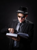 Seriously teenage boy dressed in suit reading book Royalty Free Stock Photography