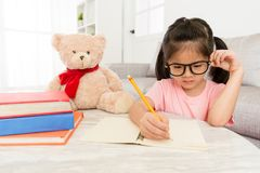 Seriously young girl kid student studying english. Knowledge at home and writing homework during holiday with her teddy bear toy Royalty Free Stock Photography