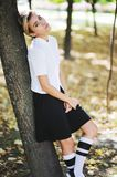 Seriously, young teen girl in a school uniform is resting at recess, leaning against tree in autumn park and looking Royalty Free Stock Photo