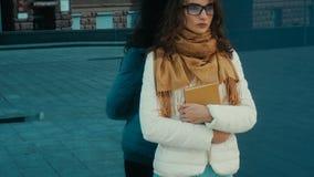 Seriout ung brunett i exponeringsglasställningar över en blå spegelvägg med böcker i händer lager videofilmer
