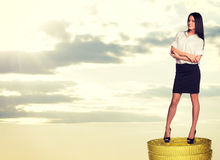 Seriuos businesswoman standing on coins stack Stock Photos