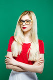 Seriuos Girl Wearing Eyeglasses, Red Top and White Skirt on Green Background. Portrait of Young Beautiful Woman with Stock Photos