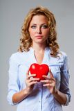 Seriuosly woman holding red heart symbol Stock Photography