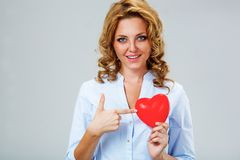 Seriuosly woman holding red heart symbol Stock Photos