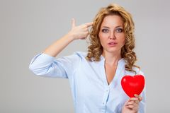 Seriuosly woman holding red heart symbol Royalty Free Stock Photography