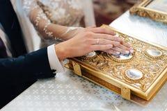 Serment aux nouveaux mariés sur la bible luxueusement décorée, les mains des hommes et les femmes dans l'église près de l'autel Photos stock
