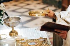 Serment aux nouveaux mariés sur la bible luxueusement décorée, les mains des hommes et les femmes dans l'église près de l'autel Photographie stock