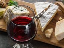 Serowy półmisek z błękitnymi serami, owoc, dokrętkami i winem na kamiennym tle, Smakowity serowy starter fotografia royalty free