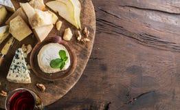 Serowy półmisek z serami, owoc, dokrętkami i winem na drewnianym tle organicznie, Odgórny widok Smakowity serowy starter obraz stock
