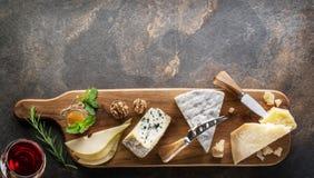 Serowy półmisek z serami, owoc, dokrętkami i winem na kamiennym tle organicznie, Odgórny widok Smakowity serowy starter fotografia stock