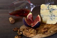 Serowy roquefort z figami, dokrętkami i szkłem czerwone wino na wo, Obrazy Royalty Free
