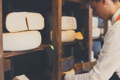 Serowy sklepowy asystent wybiera niektóre ser Obrazy Stock