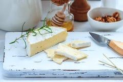 Serowy talerz słuzyć z krakers, miodem i dokrętkami, Camembert na białej drewnianej porci desce nad białym tekstury tłem zakąska Obrazy Royalty Free