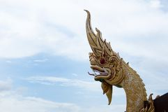 Big golden Naga statue with blue and white sky background. The serpent deity in Buddhist `Naga` golden head with blue and white sky showing what Thai people Royalty Free Stock Images