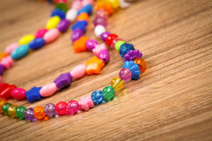 Serpente delle perle colorate su un fondo di legno Immagine Stock