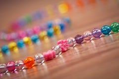 Serpente delle perle colorate su un fondo di legno Immagini Stock Libere da Diritti