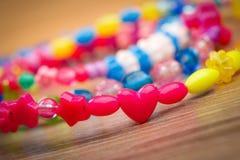 Serpente delle perle colorate su un fondo di legno Fotografia Stock Libera da Diritti