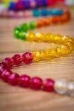 Serpente delle perle colorate su un fondo di legno Immagine Stock Libera da Diritti