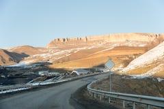 Serpentina della montagna attraverso il villaggio nelle montagne di Caucaso con le rocce epiche sul retro del polan Segnale strad Fotografie Stock Libere da Diritti
