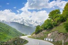 Serpentina vazia da estrada nas montanhas, no céu azul com nuvens, nos picos de montanha na neve e no fundo dos montes verdes foto de stock