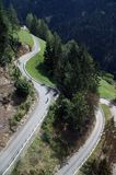 Serpentine with cyclist. Steep road/way/street with serpentines in the Alps with cyclist, Italy (South Tyrol royalty free stock image