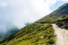 A serpentine path going down in the Carpatian mountains and a bi Stock Images