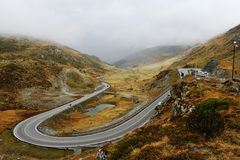Serpentine road in autumn alps Royalty Free Stock Photo