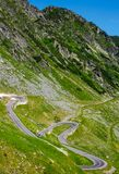 Serpentine road in Fagarasan mountains. Lovely transportation background. Popular tourist destination of Romania Royalty Free Stock Photos