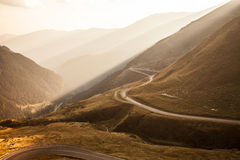 The serpentine road through sunlit mountains Stock Photography
