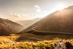 The serpentine road through sunlit mountains Stock Photos