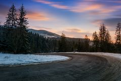 Serpentine in winter mountains at sunset. Gorgeous landscape with dark spruce forest on hillsides and red clouds on a blue evening sky. lovely transportation Stock Image