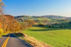 Serpientes de la carretera con curvas a través de Autumn Countryside Fotos de archivo libres de regalías