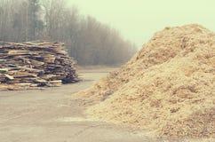 Serração Waste sob a forma de uma pilha de placas e de uma montanha da serragem Imagens de Stock