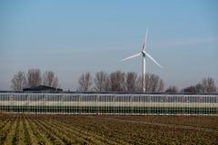 Serra con un mulino a vento contro all'inizio di febbraio il cielo immagini stock libere da diritti