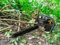 A serra de cadeia encontra-se na terra entre os ramos da interrupção do arbusto fotos de stock royalty free