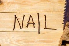 Serra e prego oxidados na tabela de madeira Fotografia de Stock Royalty Free