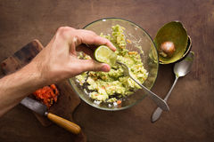 Serrage de la chaux sur la préparation de guacamole image stock